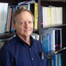 Rand Wilcox. Professor of Psychology at the USC Dornsife College, portrait photo standing in front of a shelf with books.