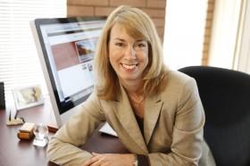 Adrianna Kezar, professor of Higher Ed at USC Portrait photo at her desk
