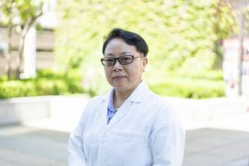 Jing Liang, MD, PhD portrait outside, Research Professor of Clinical Pharmacy in the Titus Family Department of Clinical Pharmacy.