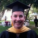 David Schwartz of the USC Dornsife College, photographed wearing a graduation cap and gown, smiling into the camera.