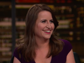 Christina Bellantoni, photo screenshot from her guest appearance on Real Time with Bill Maher, smiling off camera, wearing a black dress.