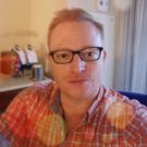 Terry Church, assistant professor at the USC Pharmacy School, selfie style photo taken in their office, wearing glasses and a red plaid button shirt.