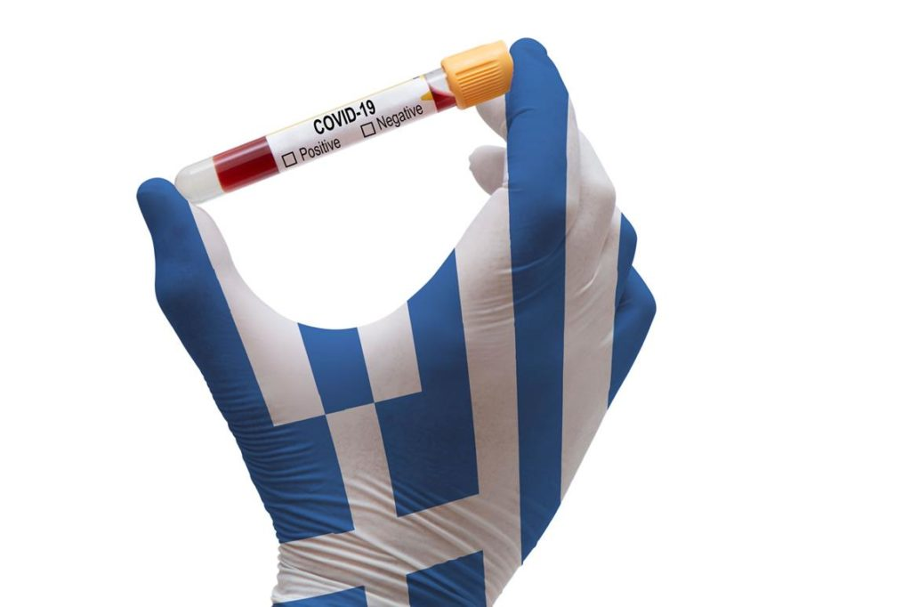 A hand wearing a Greece themed color glove holding a vial.